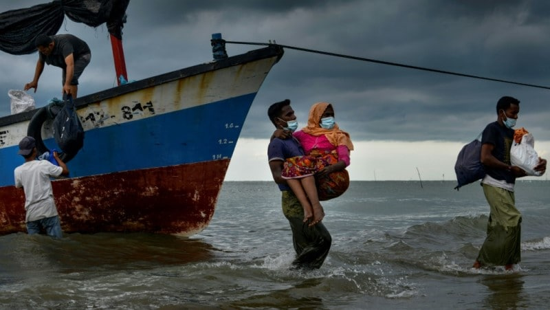 Acehnesse Fishermen Help Carry a Rohingya Child Ashore.afp