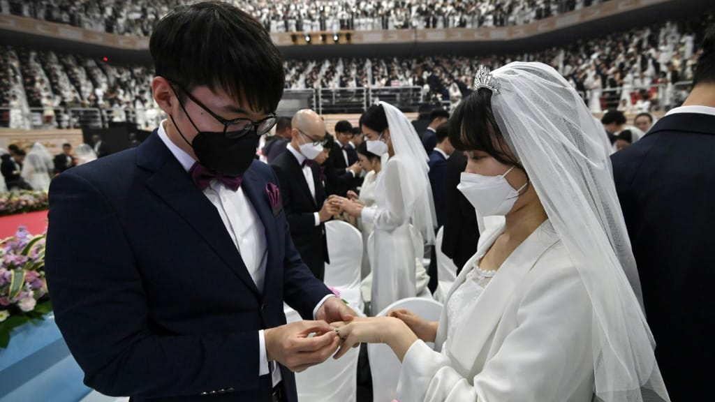 Couples in Facemask South Korea Mass Wedding.afp
