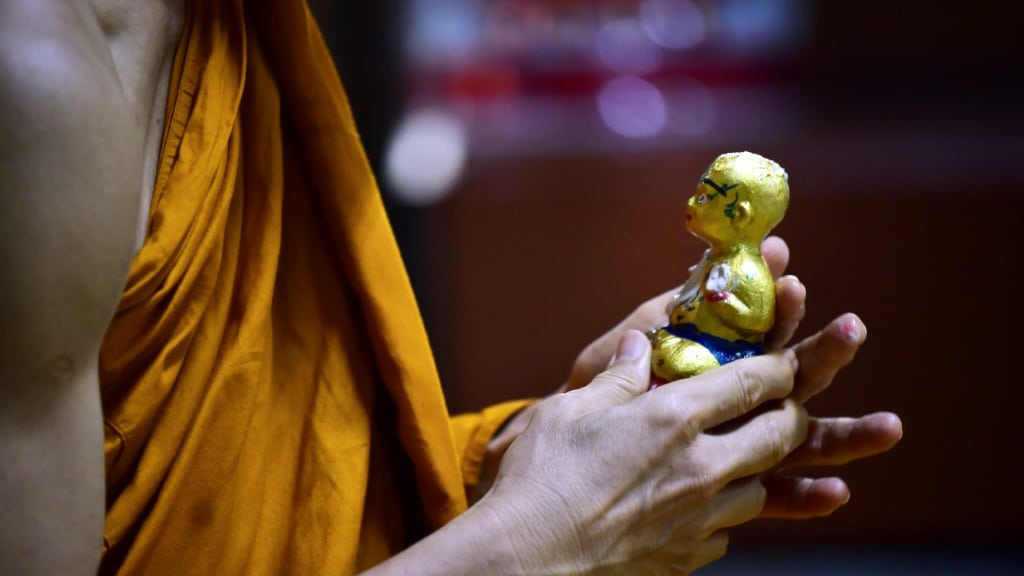 Older Thais Venerate the Protective Powers of the Golden Son.afp
